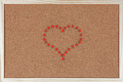 Heart made of pushpins on corkboard Royalty Free Stock Photos