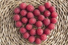 Heart made of raspberries on rustic background. Foreground Royalty Free Stock Image