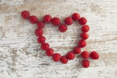 Heart made of raspberries on white wooden background pierced by stock photography