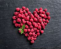 Heart made of raspberry on black slate. Top view. High resolution product Royalty Free Stock Image