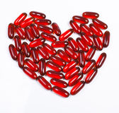 Heart made of red capsule Stock Images