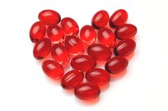 Heart made of red capsules Stock Photos