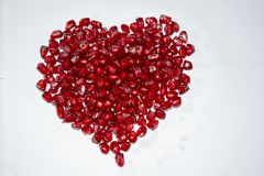 Heart made of red juicy pomegranate seeds with white background. stock images