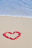 A heart made from red petals at seaside Stock Image