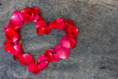 Heart made of red petals on wooden Royalty Free Stock Photography