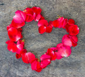 Heart made of red petals on wooden Royalty Free Stock Image