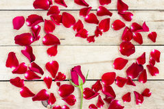 Heart made of red petals on wooden Royalty Free Stock Photos