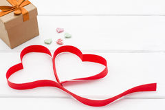 Heart made of red ribbon, a few little hearts and gift box on white wooden background. Stock Images