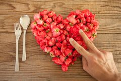 Heart made of red roses in wooden background, covered by an hand. To represent personal feelings royalty free stock image