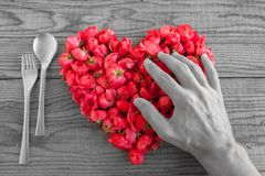 Heart made of red roses in wooden background, covered by an hand. To represent personal feelings, black and white effect royalty free stock photo