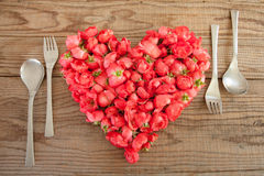 Heart made of red roses in wooden background. Covered by an hand to represent personal feelings stock images