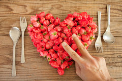 Heart made of red roses in wooden background, covered by an hand. To represent personal feelings stock photo