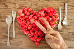 Heart made of red roses in wooden background, covered by an hand. To represent personal feelings stock photos