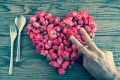 Heart made of red roses in wooden background, covered by an hand. To represent personal feelings, denin vintage effect stock photo