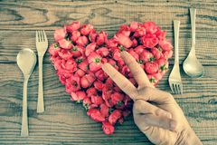 Heart made of red roses in wooden background, covered by an hand. To represent personal feelings, denin vintage effect royalty free stock images