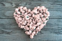 Heart made of red roses in wooden background to represent person. Al feelings, denim effect stock photo