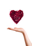 Heart made with red sparkles on hand against white background Royalty Free Stock Image