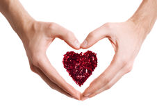 Heart made with red sparkles in hands in shape of love heart Stock Photos