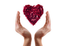 Heart made with red sparkles with two isolated hands Stock Photo