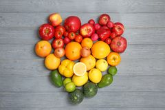 Heart made of ripe fruits and vegetables. In rainbow colors on wooden background, top view royalty free stock images