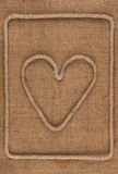 Heart made of rope on burlap Stock Photography