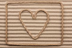 Heart made of rope lies on wavy sand. View from above stock photography
