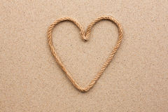 Heart made of rope on the sand. With place for your text stock photo
