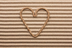 Heart made of rope on the sand. With place for your text royalty free stock photos