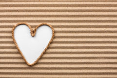 Heart made of rope with a white background on the sand. With place for your text stock photos
