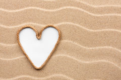 Heart made of rope with a white background on the sand. With place for your text royalty free stock photo