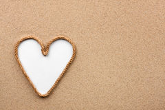 Heart made of rope with a white background on the sand. With place for your text stock photo