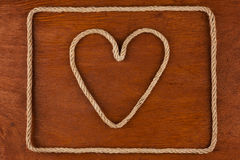 Heart made of rope on a wooden surface Stock Photography