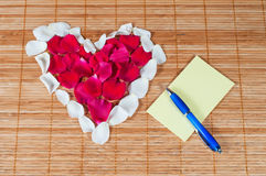 Heart made of rose petals, blank note and pen Royalty Free Stock Photos