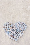 Heart made of round stones. Heart made of colorful round stones on sand at beach stock images