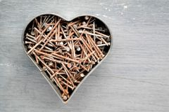 Heart made of rusted nails. Lots of nails and put together in a heart shape, processed with a silvery filter, top view Royalty Free Stock Images