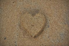 Heart made of sand. On the beach. Golden sand. Summer love stock photography