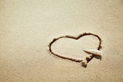 Heart made of sand on the beach. Love concept. Shell is the symbol of arrow royalty free stock images