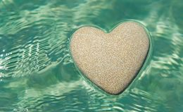Heart made of sand floating in transparent ocean ripples water b. Heart made of sand floating in transparent turquoise ocean ripples water background, Saint stock photos