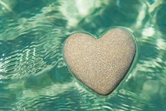 Heart made of sand floating in transparent ocean ripples water b. Heart made of sand floating in transparent turquoise ocean ripples water background, Saint royalty free stock photos