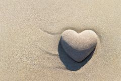 Heart made of sand with shadow on sandy beach background, Saint. Valentines day greeting cards, romantic, love, honeymoon, proposal or wedding concept royalty free stock photos