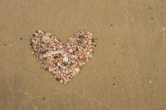Heart made of sea shells lying on a beach sand. In summer stock images