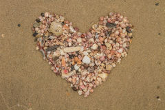 Heart made of sea shells lying on a beach sand. In summer royalty free stock photo