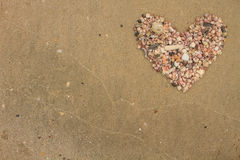Heart made of sea shells lying on a beach sand. In summer royalty free stock photography