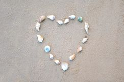 A heart made of shells on the sand.  royalty free stock photos
