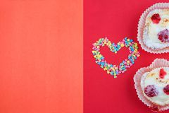 Heart made with small candy hearts, pink, red, blue white colors with two cakes on red background. Love, Valentine`s day concept. royalty free stock image