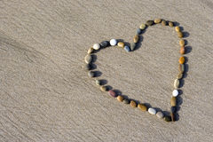 Heart made with small stone in the sand. Heart made with small stone in the wet sand stock photo