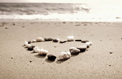 Heart made of small stones on sand Stock Photography