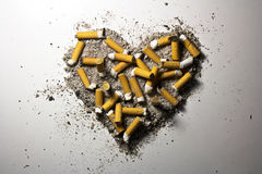 Heart made of smoked cigarettes and ash Stock Photography