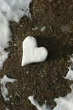 Heart made of snow on thawed Stock Photo