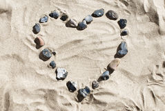 Heart made of stones at the beach. Heart made of stones lying in the sand royalty free stock photo